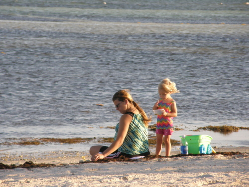 mother sitting facing the ocean sifting the beach sand and young daughter standing behind her throwing sand in the wind